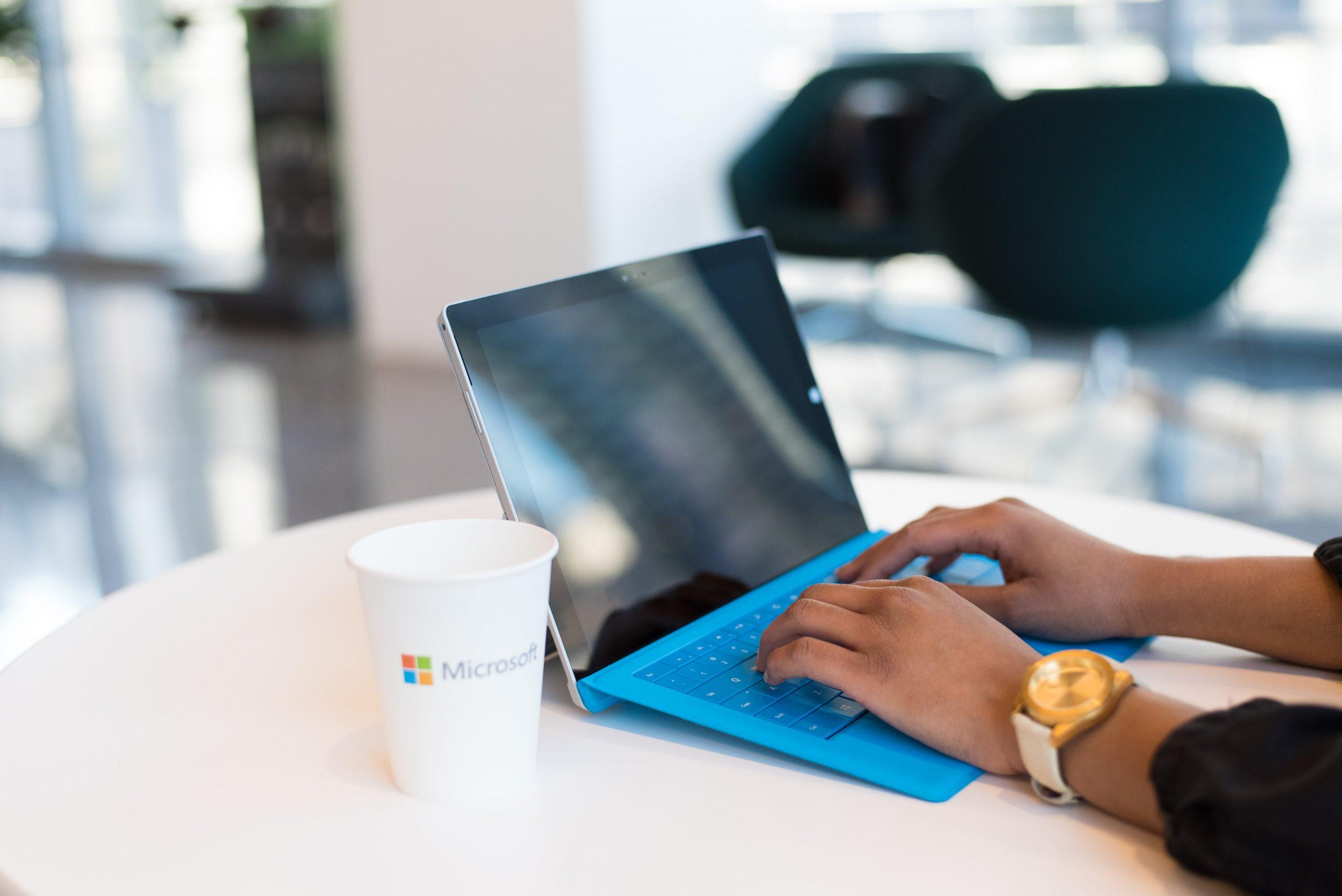 Tablette Microsoft avec tasse en carton et mains